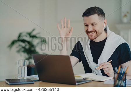 Cheerful Bearded Man Has Video Conference Online Waves Palm In Laptop Computer Uses Wireless Earphon