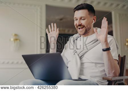 Happy Male Blogger Talks With Followers Waves Palms At Camera Of Laptop Computer Expresses Joy Talks