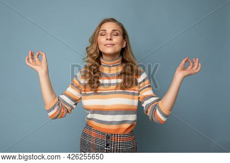 Portrait Of Young Attractive Blonde Curly Woman With Sincere Emotions Wearing Trendy Striped Pullove