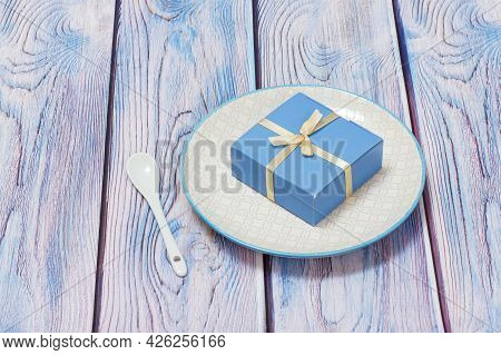 Porcelain Plate And Gift Box On Wooden Background.