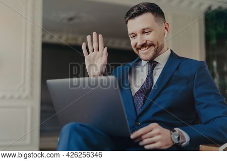 Positive Male Corporate Worker Makes Video Call Via Laptop Computer And Earbuds Waves Hello With Pal