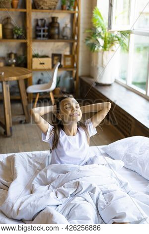 Vertical Photo Of A Ten-year-old Girl Woke Up Smiling And Stretching In Home Interior.