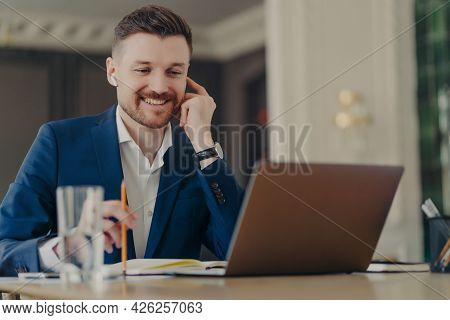 Successful Businessman In Wireless Earphones Holding Web Conference At His Office With Employees, We