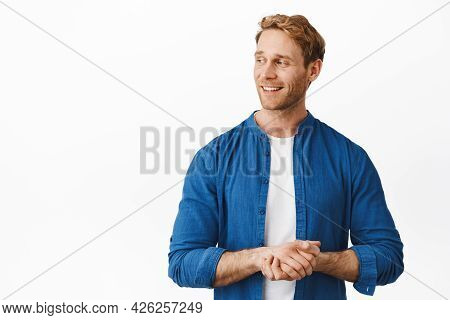 Handsome Redhead Man Hold Hands Clenched Together, Turn Head And Look At Logo Promo, Smiling Pleased