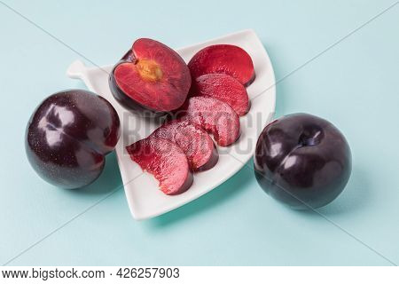 On A White Saucer There Is A Large Plum Cut Into Wedges, Next To It There Are Two More Plums. The Pu