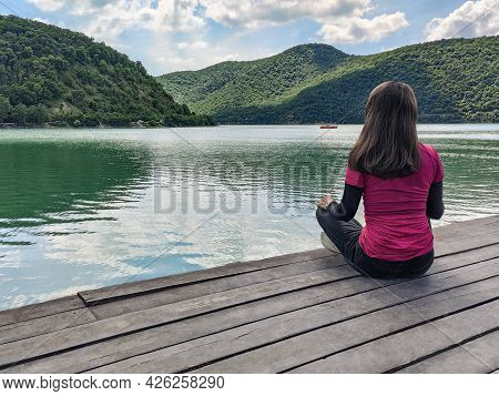 Woman Sitting On Wooden Floor And Looking At Water. Abrau-durso Lake