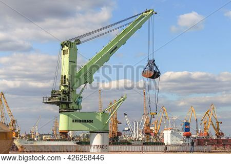 Odessa, Ukraine, October 9, 2012: Green Floating Crane Of Liebherr Company With A Raised Bucket In T
