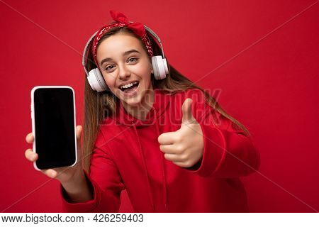 Attractive Joyful Smiling Brunette Girl Wearing Red Hoodie Isolated On Red Background Holding And Sh