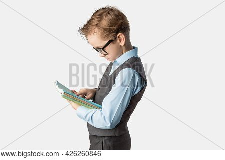 Caucasian Schoolboy In Uniform With Notebooks In His Hands And Glasses On A White Isolated Backgroun