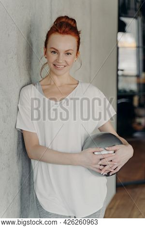 Portrait Of Young Motivated Sportive Redhaired Fitness Woman Standing In Gym With Small Exercise Bal