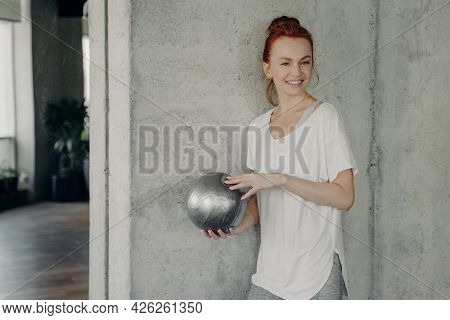 Happy Redhead Woman Against Gray Wall With Small Silver Fitball In Hand, Smiling And Tuning In To Ba