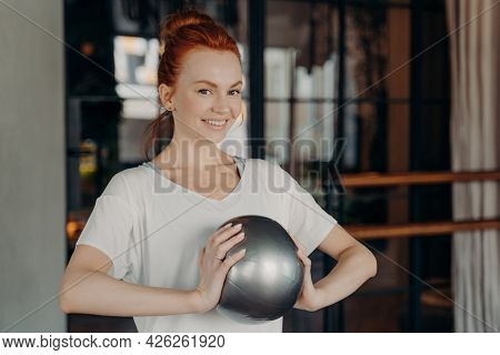 Portrait Of Lovely Ginger Woman In Sportswear Smiling At Camera While Exercising In Fitness Studio W