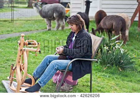 Woman Spinning Alpaca Wool Outdoors