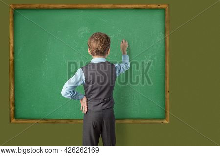 A Caucasian Schoolboy In A School Uniform Stands With His Back To The Camera And Writes On A Blackbo