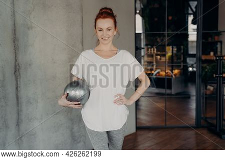 Red Haired Young Smiling Woman Standing With Fitball In One Hand Wears White Sport Tshirt And Gray L