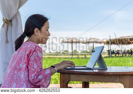 Woman Freelancer Sitting In Outdoor Cafe And Working On Laptop