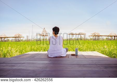 Woman Sitting On Wooden Floor With Thermos Bottle Look At Beautiful Landscape