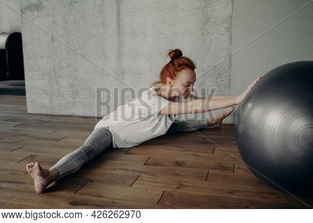 Stretching Training. Young Fit And Sportive Woman Exercising With Fitball In Fitness Studio While Si