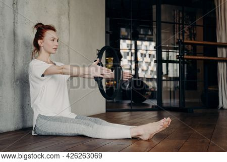 Side View Of Young Focused Sportive Female Sitting On Floor With Outstretched Legs In Fitness Studio