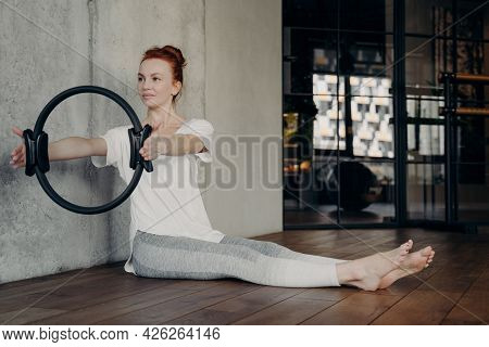 Young Active Red Haired Lady Sitting With Legs Stretched Forward And Holding Pilates Ring By Both Ha