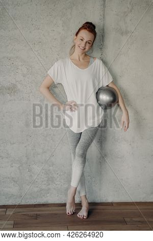Body Shaping. Full Legth Shot Of Young Beautiful Sporty Woman With Small Silver Fitball Relaxing Aft