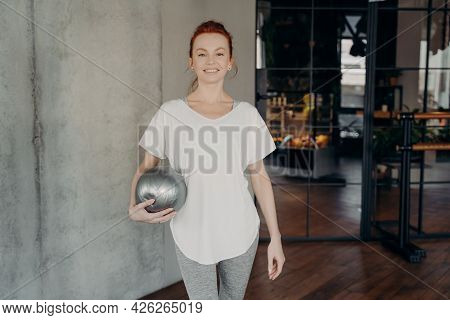 Young Happy Red Haired Sportive Woman Standing In Fitness Studio Holding Silver Fitball And Looking