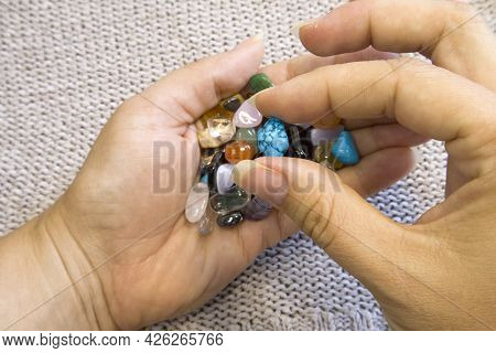 Collection Of Semi-precious Gemstones In Woman Hands On Blurred Grey Knitted Background Close Up Top