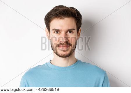 Close Up Of Young Handsome Man With Beard, Smiling At Camera With Confidence, Standing Over White Ba