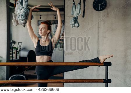 Young Red Haired Woman Ballerina Exercising In Dance Studio, Standing With One Leg On Ballet Barre A