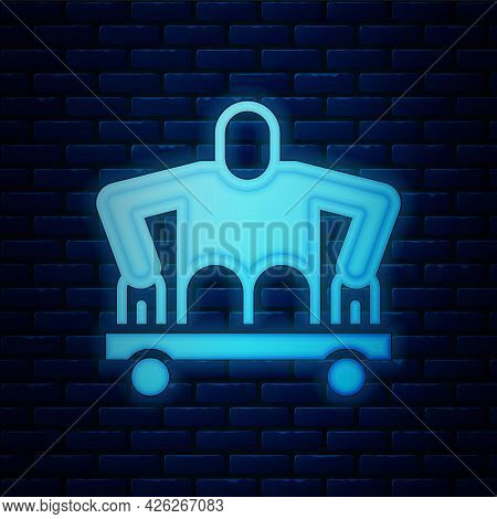 Glowing Neon Man Without Legs Sitting Wheelchair Icon Isolated On Brick Wall Background. Disability