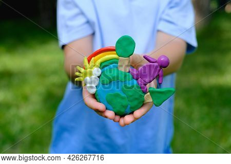 Child Hands Holding Earth Model With Clay Rainbow. Ecology Concept. Top View