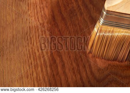 Painting A Wooden Surface With Varnish, A Brush On An Oak Board, Housework, Copy Space.