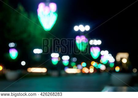 Blurred Street Of The Night City Illuminated By Lanterns And Decorated With Illumination. Soft Focus
