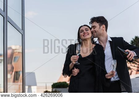 Happy Man Holding Bottle Of Champagne Near Cheerful Girlfriend In Faux Fur Jacket