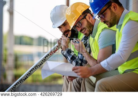 Business Building Teamwork People Concept. Group Of Engineer With Blueprint On Construction Site