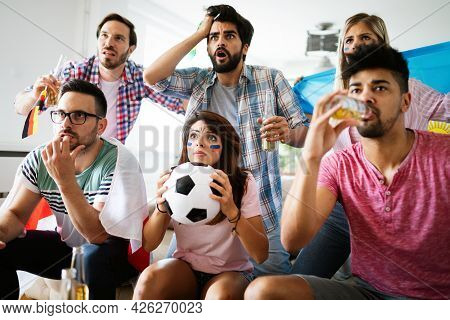 Group Of Football Fans Disappointed And Happy Watching A Football Game On The Couch.