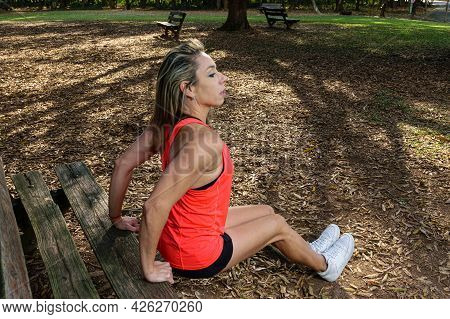 42 Years Old Brazilian Woman Doing Triceps Exercise (dips) On A Wooden Bench In A Public Square.