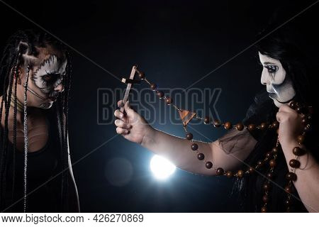 Two Supernatural Entities At War, One Using A Rosary Against The Other, Black Background, Low Key Po