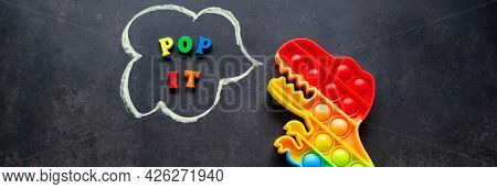 Banner With Pop It Dinosaur Toy Rainbow Colors On A Black Background With Multicolored Letters And T