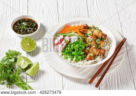 Tofu Poke Bowl With Basmati Rice, Edamame Beans, Radish, Thinly Sliced Cucumber And Carrots In A Whi