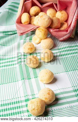 Brazil Cheese Bread, Cheese Buns Falling From A Box Onto A Green Checkered Tablecloth, Selective Foc
