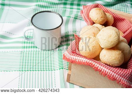 Brazil Cheese Bread, Box With Cheese Buns And A Cup On A Green Checkered Tablecloth, Selective Focus