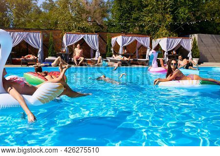 Group Of Friends Chilling In Private Villa Swimming Pool Lie In The Sun On Inflatable Flamingo, Swan