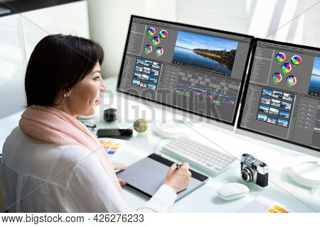 Young Female Editor Editing Video On Computer In Office