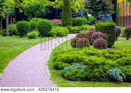 Pedestrian Pavement Of Stone Tiles In Park With Landscaping And Green Plants Bushes With Trees, Land