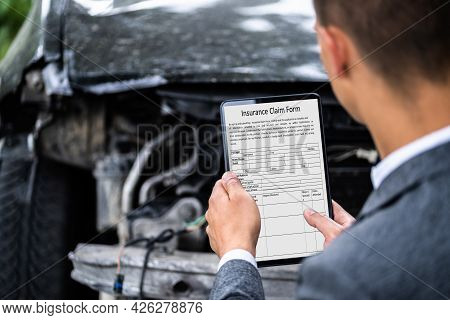 Insurance Agent Inspecting Damaged Car With Digital Tablet