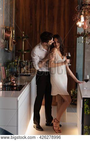 Man Seducing Smiling Girlfriend In Slip Dress With Glass Of Wine