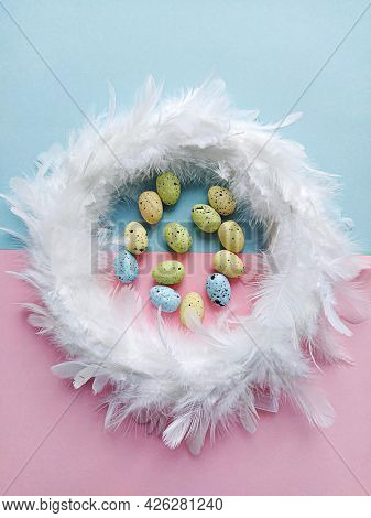 Feather Wreath On Pink Blue Background With Mini Artificial Eggs. Easter Decoration Concept