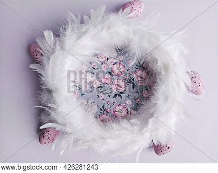 White Feathers Wreath On Lilac Floral Background With Decorative Easter Eggs, Top View