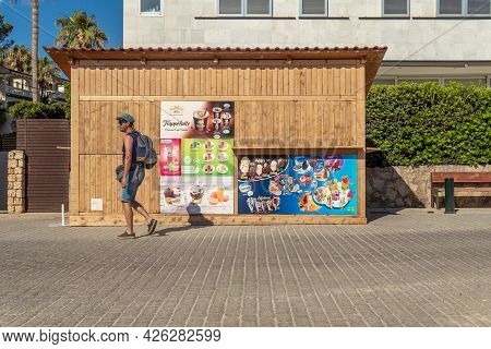 Colonia De Sant Jordi, Spain; July 02 2021: Closed Ice Cream Stand With A Tourist Walking To The Bea